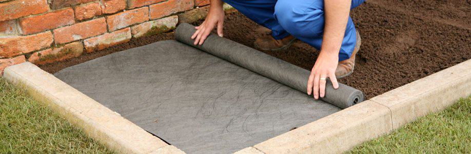 person laying weed control fabric