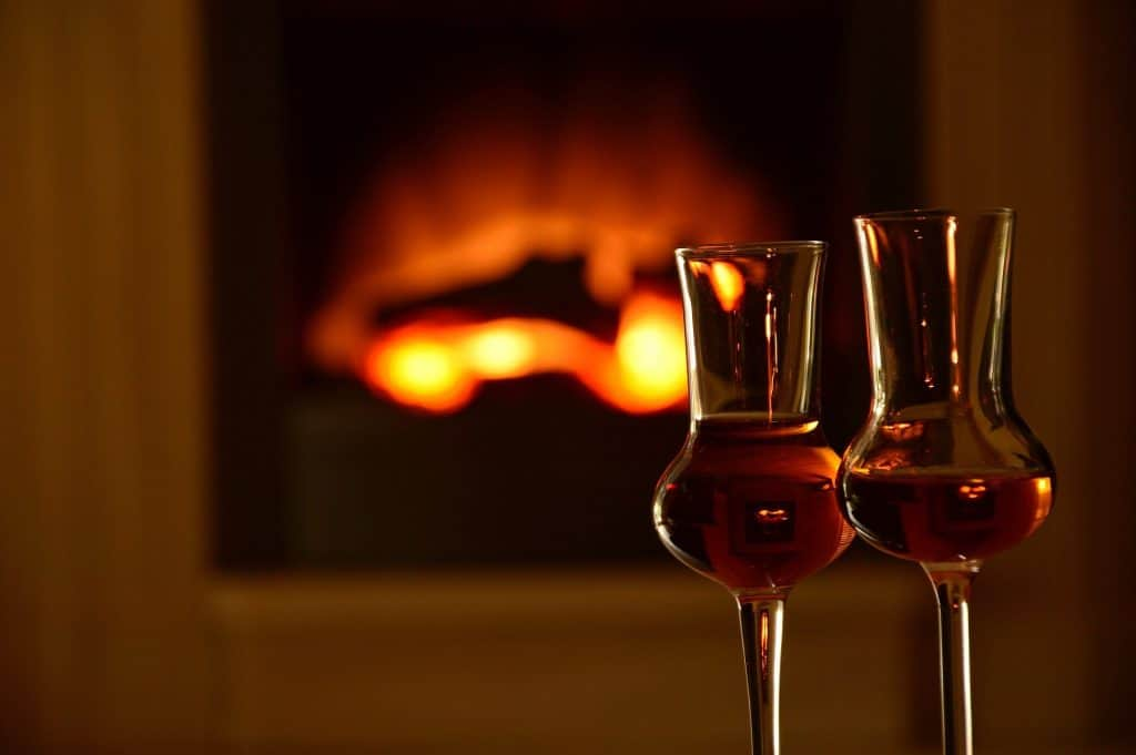 An image of two glasses in front of a cosy fire.