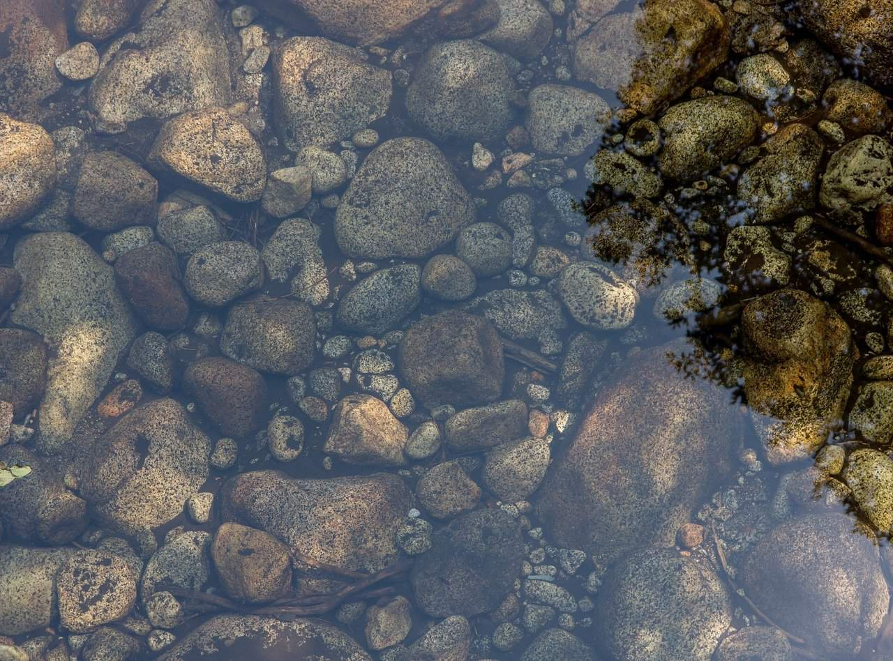 an image of stones in a pond